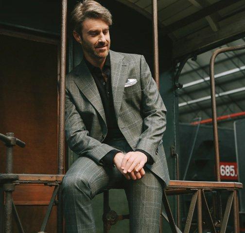 Uomo seduto su ringhiera indossa un abito grigio principe di galles con pochette bianca
