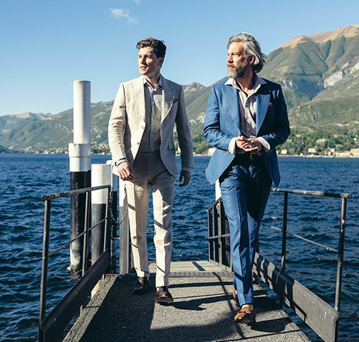 Two elegant men with beige suits and blue suits walk on a dock, in the background Lake Como, from Bellagio