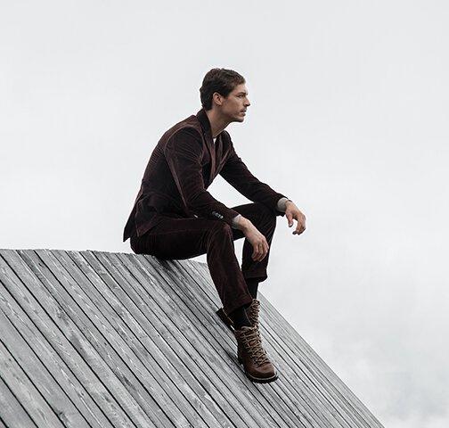 Un homme vêtu d'un costume élégant assis sur un toit