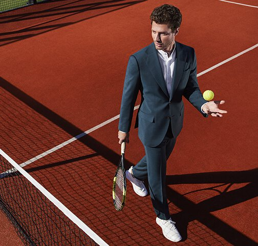 A man dressed in an elegant suit plays on a tennis court